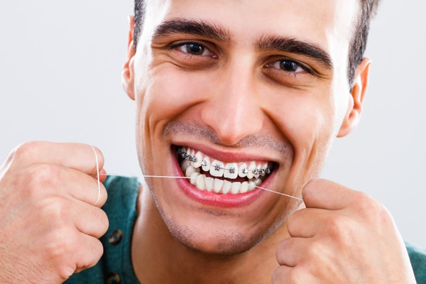 man-flossing-with-braces